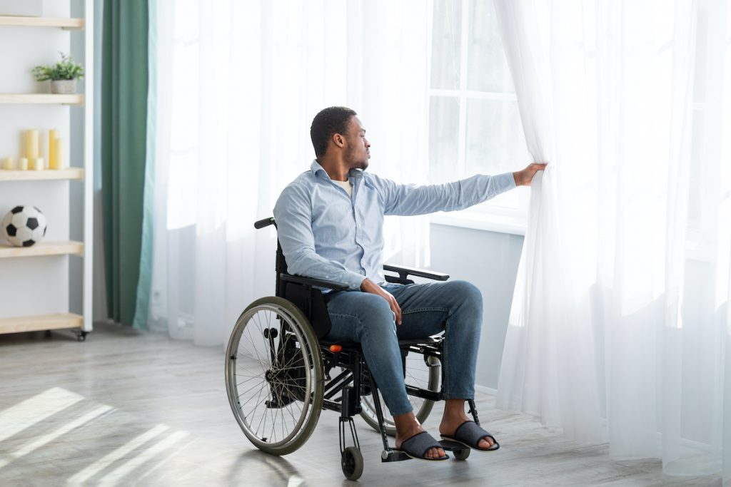 Disabled young man sitting on wheelchair looking out window