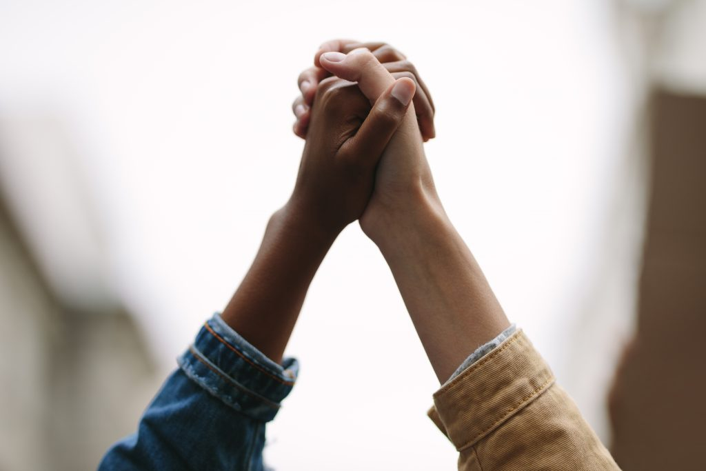 black and white person holding hands